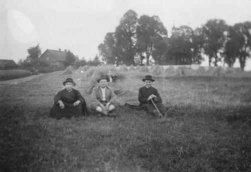 Kościół i jego najbliższa okolica [1936 r.]. Osoby na zdjęciu od lewej: ks. Stanisław Wysocki, Antoni Suliga, ks. Walenty Chyc, w tle NN. Ap.